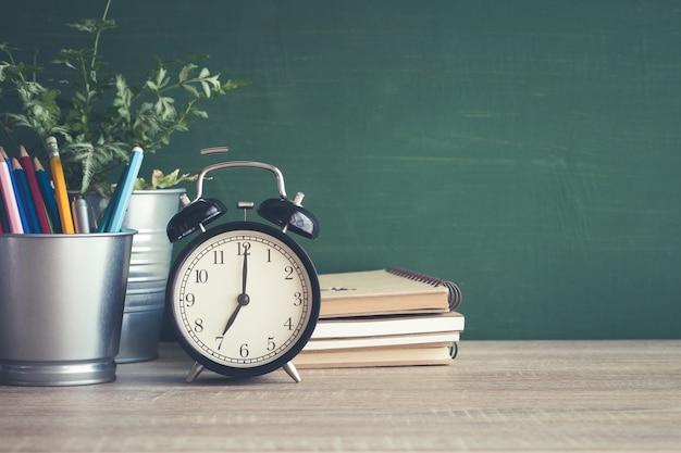 教室で黒板の背景に木製のテーブルに目覚まし時計
