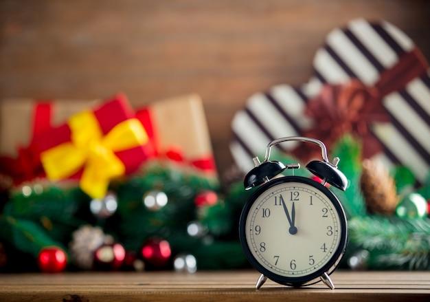 クリスマスプレゼントと木製のテーブルの上の目覚まし時計