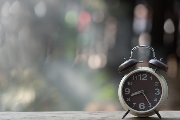 緑の自然背景のボケ味を持つ木製のテーブルの上の目覚まし時計。