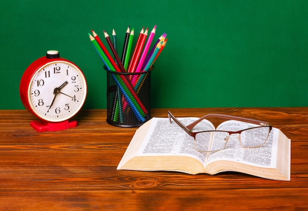 Alarm clock, open book, glasses, color pencils on a wooden table with a green background.