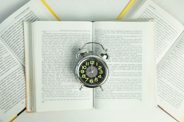 Alarm clock on the open books, top view