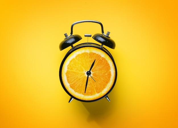 Alarm clock of orange fruit on yellow background