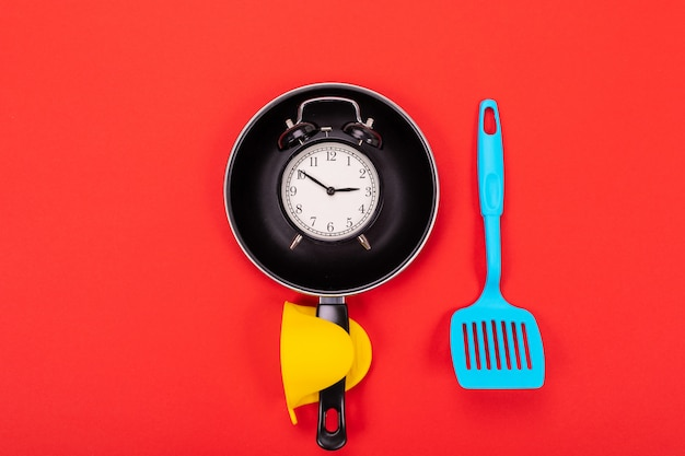 Alarm clock in pan and shovel next isolated on red