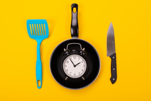 Alarm clock in pan and shovel next isolated on yellow background