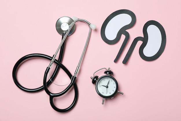 ピンクの背景に目覚まし時計、紙の腎臓と聴診器