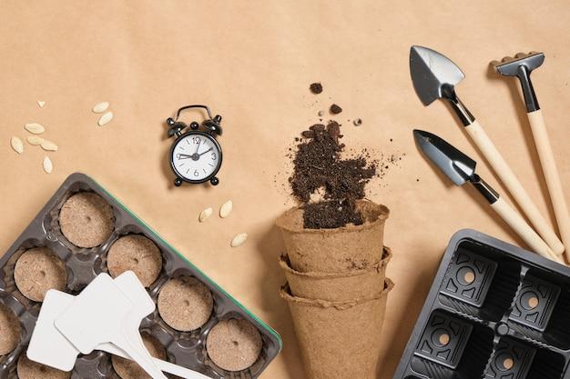 目覚まし時計、ピートポット、シャベル、ポット、プレート、クラフト紙の上面図のズッキーニシード、春の植え付け、苗の成長のためのすべて