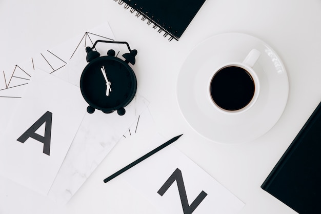 Alarm clock; pencil; diary; coffee cup and paper with letter a and n on white backdrop