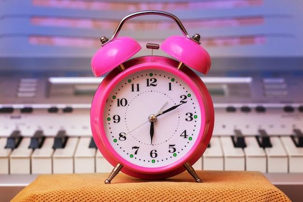 Alarm clock on piano background. music lesson_