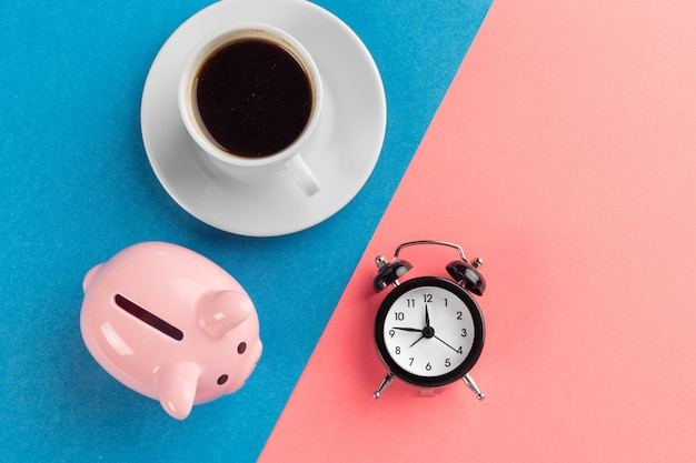 Alarm clock and piggy bank on blue and pink paper