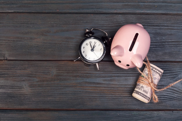 Alarm clock piggy bank on old wood table