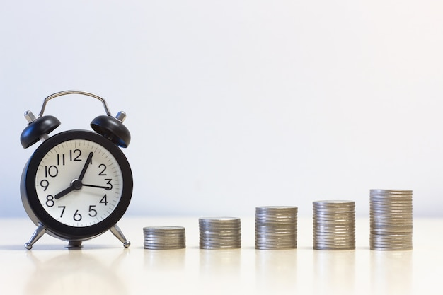 Alarm clock and a pile of coins