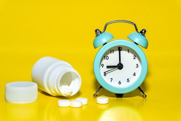 Будильник, таблетки, баночка с лекарством на желтом фоне