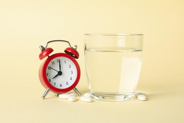 目覚まし時計、薬、ベージュの水のガラスをクローズアップ