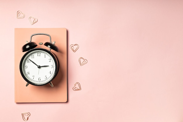 Alarm clock on pink surface with diary