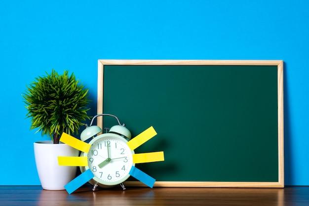 Alarm clock, plant and green chalkboard