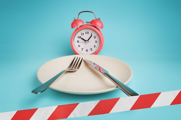 Alarm clock, plate with cutlery and barrier tape.