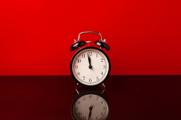 Alarm clock on red background front view