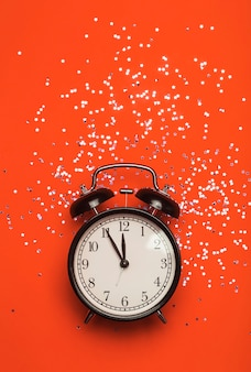 Alarm clock on a red  background with festive glitter. new year eve minimal background concept.