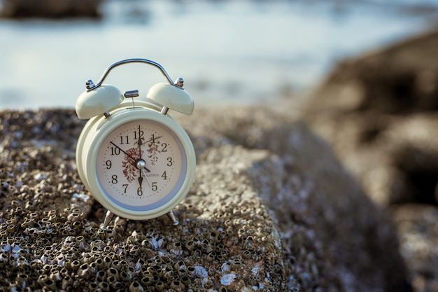 Alarm clock on the rock in morning. health and holiday concept.
