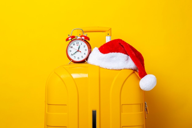 Alarm clock and santa claus hat lie on top of a yellow suitcase on a yellow background.