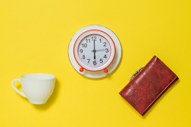 An alarm clock on a saucer, a white cup, and a woman's purse. the concept of lifting the tone in the morning.