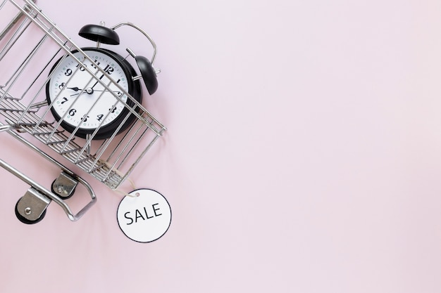 Alarm clock in shopping cart with copyspace
