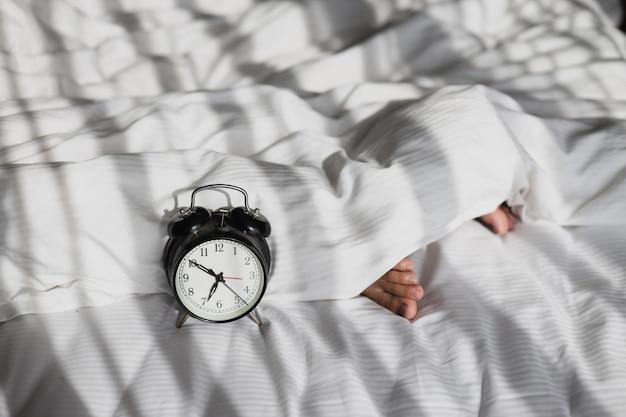 朝、毛布の上に寝ている人の足でベッドの上で7時を示す目覚まし時計