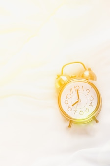 Alarm clock showing eight o'clock lying on white bed blanket in bedroom.