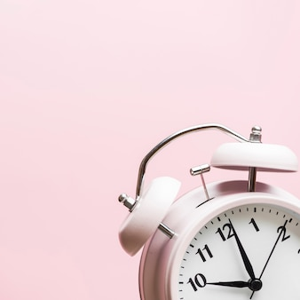 Alarm clock showing the time 10'o clock against pink background
