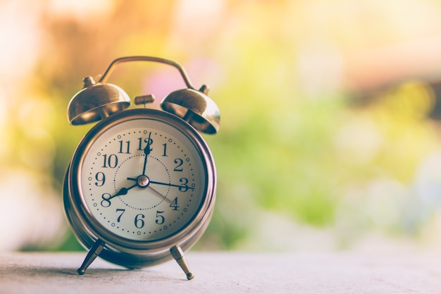 Alarm clock showing time 8 am with morning sunlight and colorful nature background