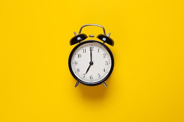 Будильник показывает час на желтом фоне