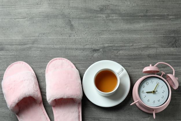 グレイの背景に目覚まし時計、スリッパ、お茶