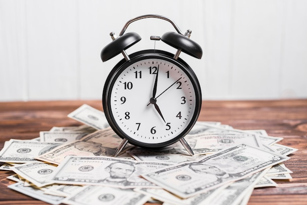 Alarm clock on spread currency notes over wooden textured background