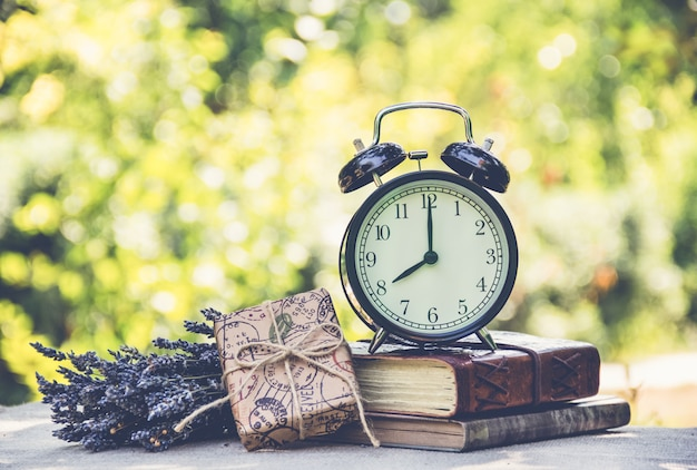 Alarm clock on stack of books on green background.