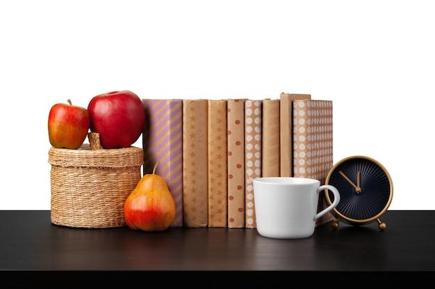 白い背景の上の卓上に本とカップの目覚まし時計のスタック