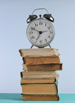 Alarm clock on stack of old books on woden shelf against the white wall