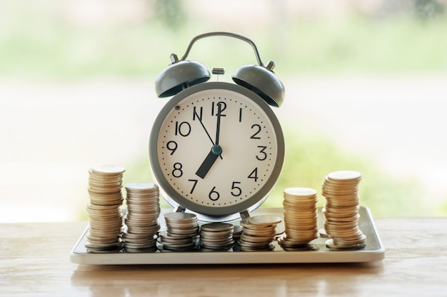 Alarm clock of stacking coins with green bokeh background