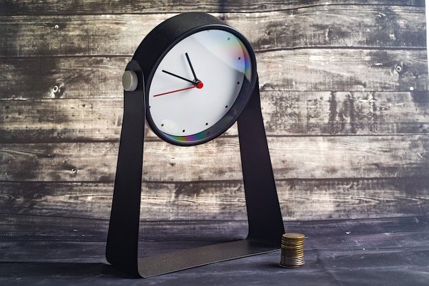 Alarm clock and stacks of coins on wooden table. business, finance, time, online shopping, money saving concept.