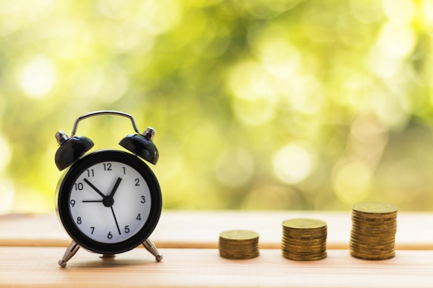 Alarm clock and stacks of coins on wooden table