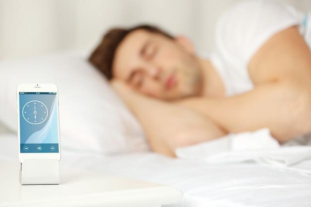 ベッドサイドテーブルの上に立っている目覚まし時計。