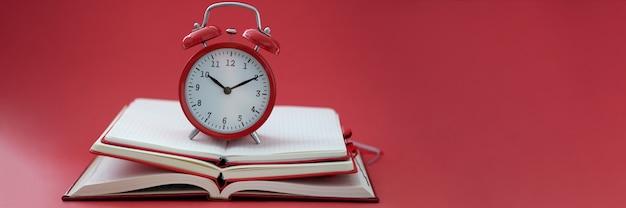 빨간색 배경 근접 촬영에 책 더미에 서 있는 알람 시계