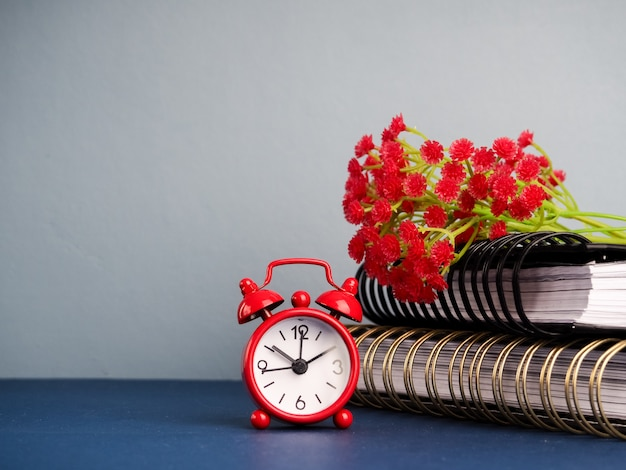 Alarm clock standing on table by stack of books against plain background