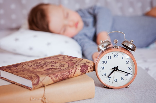 The alarm clock stands on a shelf with books, in the background the baby sleeps in a baby bed