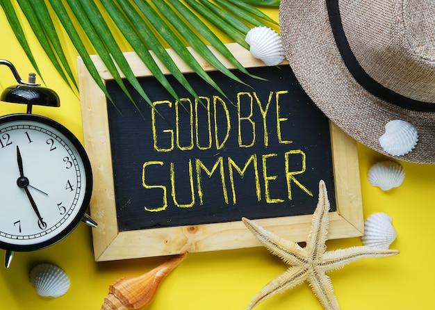 Alarm clock, starfish, fedora hat, palm leaf, sea shells and blackboa