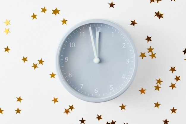 Alarm clock and stars confetti. new year concept