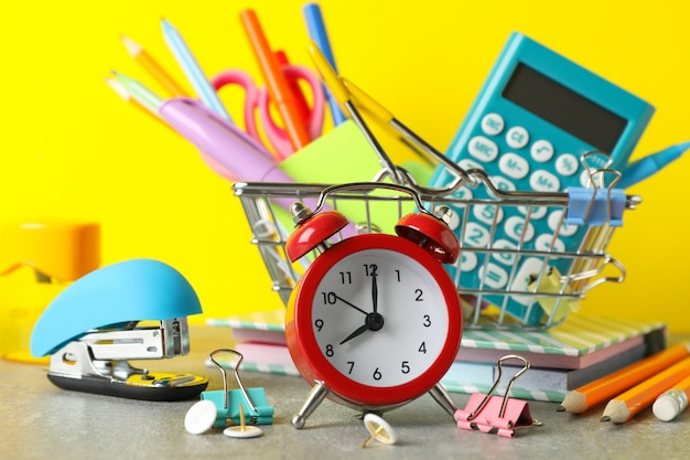 Alarm clock and stationary on grey table, close up