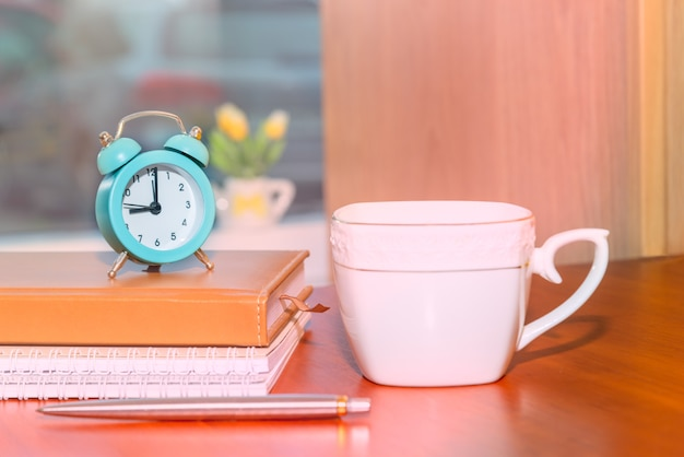 Alarm clock and stationery on books with coffee cup placed on wooden table