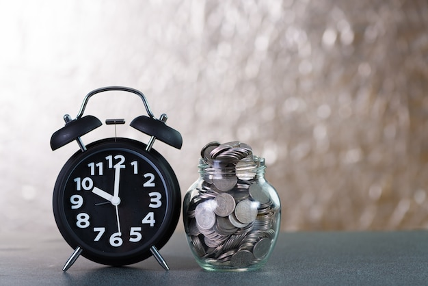 Alarm clock and step of coins stacks with coin in glass jar