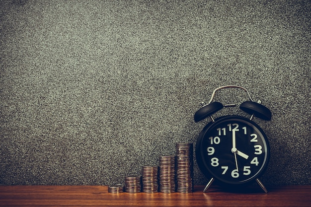 Alarm clock and step of coins stacks on working table, time for savings money concept.