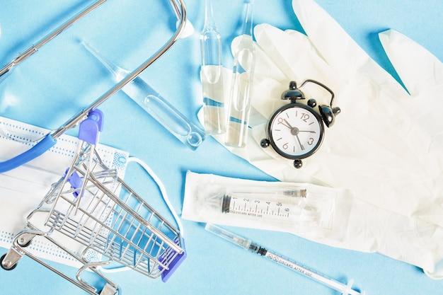 알람 시계 주사기 및 앰플 및 파란색 배경 청진기 얼굴 마스크 건강 관리 및 구매 의학 개념에 쇼핑 트롤리